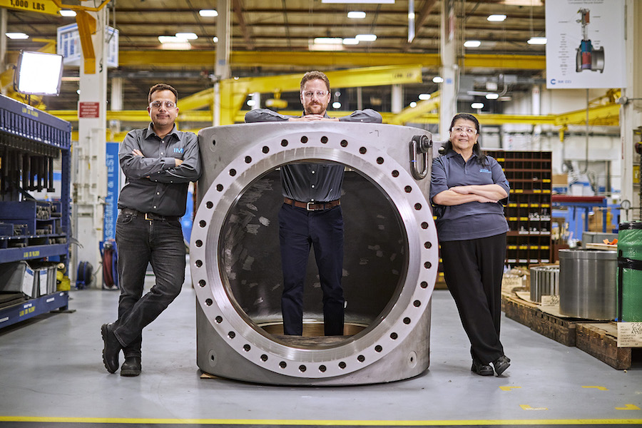 Three people standing with a large valve